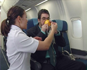 Air NZ crew member demonstrates mask to blind passenger