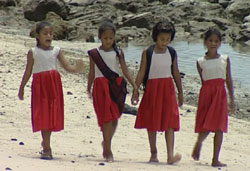 Primary school girls walk on beach in Samoa